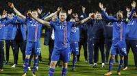 Kapten Islandia, Aron Gunnarsson, bersama rekan- rekannya melakukan selebrasi usai memastikan negaranya lolos Piala Dunia 2018 di Stadion Laugardalsvöllur, Senin (9/10/2017). Islandia menang 2-0 atas Kosovo. (AP/Brynjar Gunnarsson)