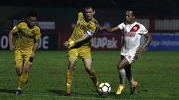 Bek Bhayangkara FC, Vladimir Vujovic, berebut bola dengan gelandang PSM Makassar, Rahmat, pada laga Liga 1 di Stadion PTIK, Jakarta, Senin (3/12). Kedua klub bermain imbang 0-0. (Bola.com/Yoppy Renato)