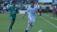 Bek Bali United, Dias Angga Putra (putih), berusaha mengamankan bola dari kejaran pemain PSS, Sidik Saimima, di Stadion Maguwoharjo, Rabu (6/11/2019). (Bola.com/Vincentius Atmaja)