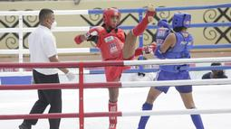 Atlet Muaythai NTT, Susanti Ndapataka (merah) bertarung dengan atlet Muaythai Papua, Iriani Labagai (biru) saat babak penyisihan Muaythai kelas 70 kg putri di GOR STT Gidi, Sentani, Papua, Rabu (29/9/2021). (FOTO : PBPON XX PAPUA/Dhoni Setiawan)