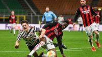 Striker Manchester United, Daniel James (kiri) terjatuh saat perebutan dengan bek AC Milan, Fikayo Tomori dalam laga leg kedua babak 16 besar Liga Europa 2020/2021 di San Siro Stadium, Milan, Kamis (18/3/2021). Manchester United menang 1-0 atas AC Milan. (AFP/Marco Bertorello)