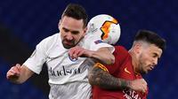 Pemain AS Roma Carles Peres (kanan) berebut bola dengan pemain Gent Sven Kums pada leg pertama babak 32 besar Liga Europa di Olympic Stadium, Roma, Italia, Kamis (20/2/2020). Gol tunggal Carles Peres membawa AS Roma menaklukkan Gent 1-0. (Alberto PIZZOLI/AFP)