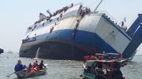 Tampak para petugas kepolisian dan penumpang kapal Wihan Sejahtera sedang melakukan evakuasi karena kapal yang ditumpangi akan karam di Teluk Lamong, Surabaya (16/11). (AFP PHOTO)