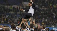 Para pemain Juventus melepar pelatih Massimiliano Allegri ke udara saat merayakan keberhasilan meraih trofi Coppa Italia di Rome Olympic stadium, (9/5/2018). Juventus menang 4-0. (AP/Gregorio Borgia)
