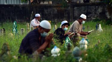 Orang-orang berdoa di sebelah makam kerabat saat perayaan Hari Raya Idul Adha di sebuah pemakaman di Provinsi Narathiwat, Thailand, Rabu (21/7/2021). Setiap Idul Adha atau hari besar Islam lainnya, sebagian warga banyak mendatangi kuburan untuk mendoakan keluarganya. (Madaree TOHLALA/AFP)