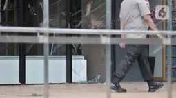 Polisi melintasi kaca salah satu kios AEON Mall Jakarta Garden City yang dirusak warga di Cakung, Jakarta Timur, Selasa (25/2/2020). Sekelompok warga menyerang fasilitas fisik AEON Mall Jakarta Garden City karena dituding sebagai penyebab permukiman mereka kebanjiran. (merdeka.com/Iqbal S Nugroho)