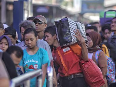Sejumlah pemudik mengantre di pintu keberangkatan Stasiun Pasar Senen, Jakarta, Selasa (12/6). Sebanyak 25 ribu lebih pemudik berangkat dari Stasiun Pasar Senen dengan tujuan yang paling banyak dituju Semarang dan Surabaya. (Liputan6.com/Faizal Fanani)