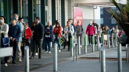 Orang-orang mengantre pada pagi hari di luar supermarket ketika Selandia Baru bersiap ke pembatasan level 3 di Hobsonville, Auckland, Rabu (12/8/2020). Selandia Baru akan memberlakukan lockdown di Auckland setelah ditemukan 4 kasus baru COVID-19 di kota itu. (Dean Purcell/New Zealand Herald via AP)