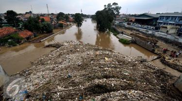 Tumpukan sampah yang tersangkut di jembatan Rawajati Kalibata, Jakarta, Selasa (8/3/2016). Hujan yang mengguyur Bogor dua hari terakhir mengakibatkan banjir kiriman yang disertai sampah batang bambu. (Liputan6.com/Helmi Fithriansyah)
