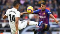 Gelandang Barcelona, Rafinha, berebut bola dengan gelandang Real Madrid, Casemiro, pada laga La Liga Spanyol di Stadion Camp Nou, Barcelona, Minggu (28/10). Barcelona menang 5-1 atas Madrid. (AFP/Gabriel Bouys)