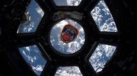 Sebuah emblem Departemen Pemadam Kebakaran Kota New York mengapung di jendela Cupola dari Stasiun Luar Angkasa Internasional pada peringatan 18 tahun serangan teror 11 September (9/11). ( NASA)