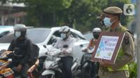 Petugas Satpol PP memegang poster himbauan kepada masyarakat tentang Covid-19, Jakarta, Jumat (6/11/2020). Upaya pemerintah tidak berhenti mengingatkan masyarakat untuk selalu mengenakan masker dan 3M agar terhindar dari bahaya penyebaran Covid-19 yang kini belum berakhir. (merdeka.com/Imam Buhori)