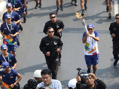 Pelari membawa obor Asian Games 2018 dalam Torch Relay Asian Games 2018 di kawasan TMII, Jakarta Timur, Rabu (15/8). Kota Jakarta menjadi persinggahan terakhir api Asian Games yang dimulai dari wilayah Jaktim dan Jaksel. (Liputan6.com/Immanuel Antonius)