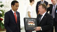 Perdana Menteri Denmark Lars Lokke Rasmussen memberikan Presiden Joko Widodo (Jokowi) cendera mata piringan hitam band Metallica usai pernyataan bersama dalam kunjungan kerja PM Denmark di Istana Bogor, Jawa Barat, Selasa (28/11). (AP/Dita Alangkara)