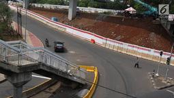 Tangga JPO di Jalan Dewi Sartika, Cawang, Jakarta Timur, berada di tengah jalan, Rabu (9/1). Adanya proyek pelebaran jalan menyebabkan posisi trotoar bergeser sehingga tangga JPO tersebut menjadi di tengah jalan. (Liputan6.com/Immanuel Antonius)