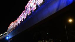 Lampu yang bisa berganti-ganti warna menghiasi jembatan penyeberangan orang (JPO) di kawasan Jakarta Timur, Kamis (27/12). Di malam hari, JPO tersebut lampu warna-warni menyala terang sehingga terlihat cantik dari kejauhan. (Merdeka.com/Imam Buhori)