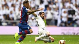 Striker Levante, Roger Marti, berebut bola dengan gelandang Real Madrid, Isco, pada laga La Liga Spanyol di Stadion Santiago Bernabeu, Madrid, Sabtu (20/10). Madrid kalah 1-2 dari Levante. (AFP/Gabriel Bouys)