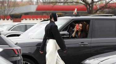 Seorang perempuan mengambil gambar model yang berjalan melewati mobil saat drive-in fashion show bagian dari Praha Fashion Week di Praha, Ceko, Sabtu (1/5/2021). Karena pembatasan virus corona, penonton hanya dapat melihat pertunjukan dari dalam mobil mereka. (AP Photo/Petr David Josek)