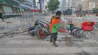 Petugas Penanganan Prasarana dan Sarana Umum (PPSU) atau Pasukan Oranye membersihkan sisa puing-puing pasca kerusuhan di MH. Thamrin, Kamis (23/5/2019). Bentrokan terjadi setelah pihak kepolisian berupaya membubarkan massa aksi yang masih bertahan di depan Bawaslu. (Liputan6.com/Herman Zakharia)