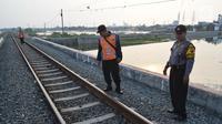 Petugas dari Polsuska dan Babinkamtibmas Kemijen Semarang  melakukan pemeriksaan rel kereta api di Jalur Kemijen, Minggu (3/6) . Pemeriksaan dilakukan secara ketat dan berkala untuk keamanan jalur kereta api selama arus mudik 2018. (Liputan6.com/Gholib)