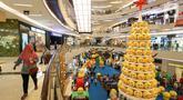 Pengunjung melintas di samping pohon Natal yang didominasi warna kuning setinggi 12 meter di Lippo Mall Kemang,  Jakarta Sabtu (14/12/2019). Pohon dengan konsep Joypixels Emoji momentum liburan menyambut Natal bersama keluarga. (Liputan6.com/Fery Pradolo)