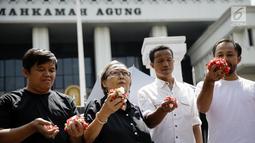 Sejumlah massa saat menggelar aksi damai di depan Mahkamah Agung, Jakarta, Rabu (7/6). Dalam aksinya mereka menaburkan bungan pada payung sebagai bentuk simbol kekhawatiran matinya keadilan dan penegakan hukum. (Liputan6.com/Faizal Fanani)