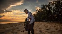 Tengku Mohamad Ali Mansor memeriksa botol kaca di sebuah pantai di desa Mangkuk, Malaysia timur pada 12 September 2020.  Upaya seorang lansia Malaysia untuk membersihkan pantai-pantai negara itu dari kaca-kaca yang terkelupas membuatnya mengumpulkan koleksi ribuan botol. (AFP/Mohd Rasfan)