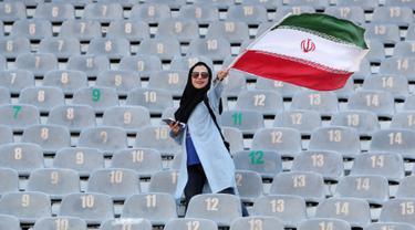 Wanita Iran mengibarkan bendera negaranya saat akan menyaksikan laga kualifikasi Piala Dunia 2022 antara Iran dengan Kamboja di Stadion Azadi, Teheran, Iran, Kamis (10/10/2019). Wanita Iran akhirnya diizinkan menonton bola dalam stadion setelah 38 tahun dilarang. (AP Photo/Vahid Salemi)