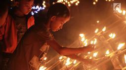Anak-anak menyalakan lampu minyak saat perayaan tumbilotohe atau penyalaan berjuta lampu minyak di akhir Ramadan di Kota Gorontalo, Jumat (31/5/2019). Lampu minyak tersebut dipasang menghiasi jalan, halaman rumah, masjid bahkan sungai. (Liputan6.com/Arfandi Ibrahim)