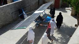 Warga melihat pesawat buatan Muhammad Fayyaz di Desa Tabur, Provinsi Punjab, Pakistan, 8 April 2019. Pesawat kecil tersebut dirakit menggunakan mesin dari alat pemotong aspal, sayapnya dari karung goni, dan roda-rodanya diambil dari roda becak. (ARIF ALI/AFP)