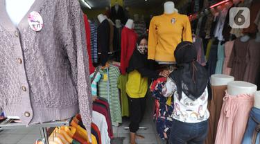 Warga membenahi  display  busana pada sebuah toko di sentra konveksi Bulak Timur, Depok, senin (11/5/2020). Jelang Lebaran 2020, pembuat dan penjual konveksi di kawasan ini mengeluhkan anjloknya penjualan hingga 80% hingga 90% akibat dampak pandemi Covid-19. (merdeka.com/Arie Basuki)