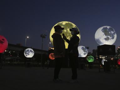 Wanita berdiri di samping instalasi bulan purnama yang bersinar di sebuah taman di Seoul, Korea Selatan, Jumat (18/9/2020). Pejabat setempat memasang bulan purnama buatan untuk meningkatkan semangat saat wabah COVID-19 sekaligus menyambut Chuseok, Thanksgiving versi Korea. (AP Photo/Ahn Young-joon)