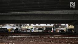 Sejumlah mobil terparkir di bawah kolong tol Becakayu Kalimalang, Jakarta Timur, Selasa (12/2). Sejumlah warga Cipinang Melayu, Makasar, menyalahgunakan lahan kosong di bawah Tol Becakayu untuk parkir liar. (Liputan6.com/Faizal Fanani)