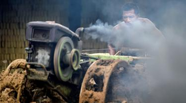 Seorang pria mencampur bahan untuk membuat batu bata di sebuah pabrik batu bata di pinggiran Kajhu, Provinsi Aceh (18/11/2020). (AFP/Chaideer Mahyuddin)