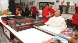 Mantan Menko Bidang Kemaritiman Rizal Ramli saat mencukur rambut di kawasan Glodok, Jakarta Barat, Kamis (15/2). Rizal menembus lorong yang tergenang air dan berdialog dengan pedagang. (Liputan6.com/Pool/Yasin)