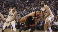 Guard Toronto Raptors Fred VanVleet (tengah) menerobos pertahanan Milwaukee Bucks pada lanjutan NBA 2017-2018 di Air Canada Centre, Jumat (23/2/2018) atau Sabtu (24/2/2018) WIB. (Chris Young/The Canadian Press via AP)
