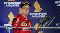 Pembalap Ferrari Sebastian Vettel berselebrasi di podium setelah memenangkan balapan Formula Satu (F1) Grand Prix Singapura di Sirkuit Jalan Marina Bay, Singapura (22/9/2019). Vettel berhasil menjuarai balapan dengan catatan waktu 1 jam:58menit:33.667 detik. (AP Photo/Vincent Thian)