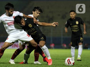 Pemain PSIS Semarang Pratama Arhan Alif Rifai (kanan) berusaha melepaskan diri dari hadangan pemain PSM Makassar Saldi dan Rasyid Assahid Bakri pada laga perempat final Piala Menpora 2021 di Stadion Kanjuruhan, Malang, Jumat (9/4/2021). PSIS vs PSM berakhir 2-4 via adu penalti (Bola.com/Arief Bagus)