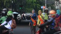 Personel Polisi Wanita (Polwan) Polres Jakarta Timur mengenakan pakaian kebaya saat mengatur arus lalu lintas di Jalan Otista Raya, Jatinegara, Jumat (20/4). Kegiatan tersebut dilakukan dalam rangka memperingati Hari Kartini. (Merdeka.com/Imam Buhori)