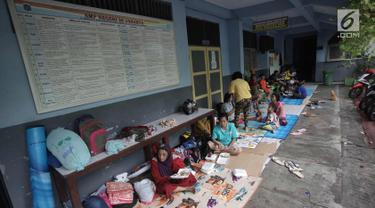 Warga yang rumahnya terendam banjir mengungsi di Gedung SMP Negeri 26, Jalan Kebon Pala, Kampung Melayu, Jatinegara, Jakarta Timur, Selasa (6/2). Sebanyak 42 KK mengungsi di tempat tersebut. (Liputan6.com/Arya Manggala)