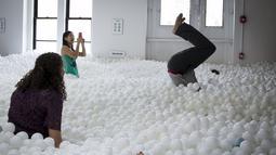 Para karyawan dan masyarakat umum saat bermain dan bersantai di kolam bola yang ada di kantor SoHo, New York City, Selasa (25/8/2015). Ada sekitar 81.000 bola putih disebar diruangan ini. (REUTERS/Mike Segar)