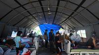 Pasien menerima perawatan di tempat penampungan sementara di luar Rumah Sakit Regional Sulbar, Mamuju, Minggu (17/1/2021). Mereka dirawat di dalam tenda darurat untuk mengantisipasi gempa susulan pascagempa 6,2 yang mengguncang Majene dan Mamuju, Sulawesi Barat pada Jumat (15/1). (ADEK BERRY/AFP)