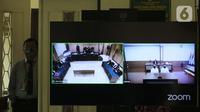 Petugas berdiri di sisi layar monitor yang menampilkan dua terdakwa penyiraman air keras terhadap penyidik KPK Novel Baswedan, Rahmat Kadir Mahulette (kanan) dan Rony Bugis yang mengikuti sidang putusan secara teleconference di PN Jakarta Utara, Kamis (16/7/2020). (Liputan6.com/Helmi Fithriansyah)