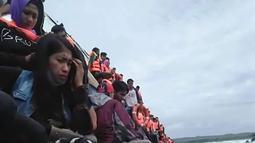 Penumpang berpegangan pada sisi kapal saat KM Lestari Maju tenggelam di lepas pantai Pulau Selayar, Provinsi Sulawesi Selatan, Selasa (3/7). KM Lestari Maju tenggelam di Perairan Selayar diduga lantaran lambung kapal bocor. (BNPB/AFP)