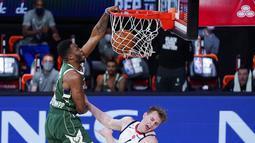 Pebasket Milwaukee Bucks, Thanasis Antetokounmpo, memasukkan bola saat melawan Washington Wizards pada laga NBA, Selasa (11/8/2020). Bucks mengalahkan Wizards dengan skor 126-113. (AP Photo/Ashley Landis, Pool)