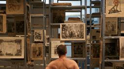Pengunjung melihat koleksi pada pameran 'Discorde, Fille de la Nuit' di museum Palais de Tokyo di Paris, 5 Mei 2018. Museum seni di Paris membuka pintunya bagi 160 orang nudis atau orang yang memilih tidak memakai busana. (AFP/GEOFFROY VAN DER HASSELT)
