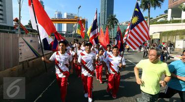 Sejumlah remaja membawa bendera negara-negara peserta Sea Games di Jakarta, Minggu (30/4). Kirab itu berlangsung guna menyambut Sea Games Kuala Lumpur 2017. (Liputan6.com/Johan Tallo)
