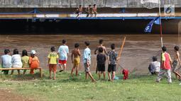 Anak-anak usai bermain sepak bola di bantaran Kanal Banjir Barat, Jakarta, Jumat (5/4). Tidak adanya lapangan menjadikan lokasi tersebut sebagai tempat bermain mereka, meskipun dalam kondisi seadanya. (Liputan6.com/Immanuel Antonius)