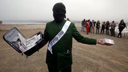 Pria membawa koper berisi uang selama melakukan tetrikal dalam partisipasi mengungkap korupsi di Lima,Peru, (12/11/2015). Acara diselenggarkan oleh organisasi non -pemerintah yang ingin menciptakan kesadaran tentang korupsi. (REUTERS/Mariana Bazo)