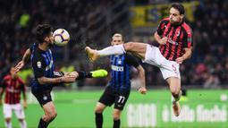 Gelandang AC Milan, Matteo Politano, berebut bola dengan gelandang Inter Milan, Giacomo Bonaventura, pada laga Serie A Italia di Stadion San Siro, Milan, Minggu (21/10). Inter menang 1-0 atas Milan. (AFP/Marco Bertorello)